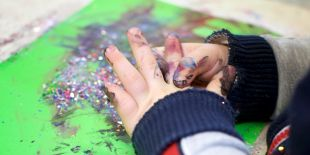 Cocoon Childcare - Child painting with glitter